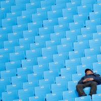 A man sleeps in an empty stand during a downhill skiing match. | REUTERS