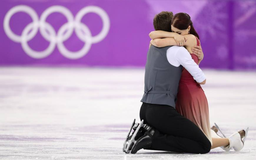 Ekaterina Bobrova and Dmitri Soloviev of Russia embrace following their performance in the ice dance free dance competition final.