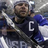 Brian Gionta, left, of the United States, is checked by Tomas Starosta, of Slovakia, during the third period of the qualification round of the men's hockey game. | AP