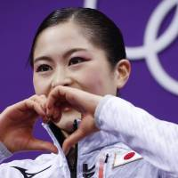 Satoko Miyahara reacts as her scores are posted following her performance in the women's short program figure skating. | AP