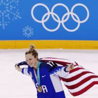 Jocelyne Lamoureux-Davidson of the U.S. holds the U.S. flag as she celebrates her team's victory over Canada in the final of the women's ice hockey competition.  | REUTERS