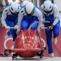 Pilot Simone Bertazzo of Italy (center) leads his team as they start the 4-man bobsleigh training session. | AFP-JIJI
