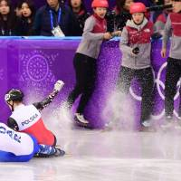 Russia's Aleksandr Shulginov and Poland's Bartosz Konopko crash in the men's 500m short track speed skating quarter-final event. | AFP-JIJI