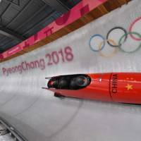 Pilot Shao Yijun of China (front) corners at turn 14 in their 4-man bobsleigh training session. | AFP-JIJI