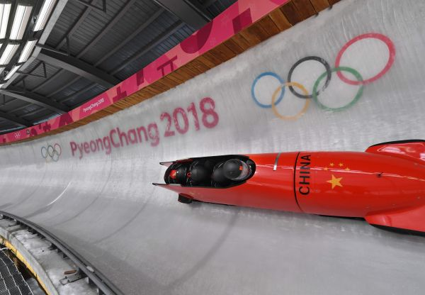 Pilot Shao Yijun of China (front) corners at turn 14 in their 4-man bobsleigh training session.