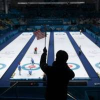 A man waves an American flag during the curling men's semi-final game between Canada and USA. | AFP-JIJI