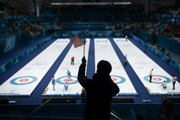 A man waves an American flag during the curling men