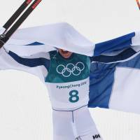 Finland's Iivo Niskanen celebrates after crossing the finish line to win gold in the men's 50-km cross country mass start classic. | AFP-JIJI
