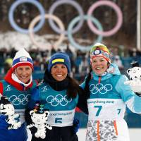 Sweden's Charlotte Kalla (center), flanked by Norway's Marit Bjoergen and Finland's Krista Parmakoski celebrate during the victory ceremony after taking first place in the women's 7.5km + 7.5km cross-country skiathlon event at the Pyeongchang 2018 Winter Olympic Games on Saturday. | AFP-JIJI