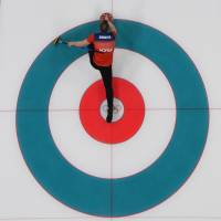 Norway's Magnus Nedregotten slides the stone during the curling mixed doubles round robin session between Norway and Finland on Saturday. | AFP-JIJI
