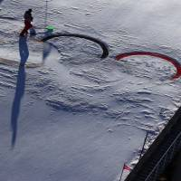 After heavy winds, a volunteer cleans the Olympic rings at the ski jumping venue. | REUTERS