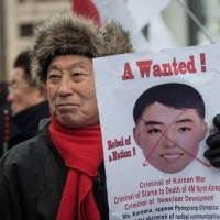 A South Korean protester holds a banner featuring the image of a mask worn by North Korean cheerleaders the previous day. The protestors accused South Korean President Moon Jae-in of allowing North Korea to stage its 'propaganda' in Seoul and undermining the military alliance with the US.  | AFP-JIJI