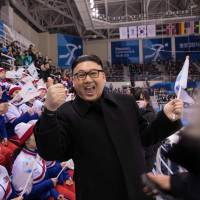 A man impersonating North Korean leader Kim Jong Un gestures as he stands before North Korean cheerleaders attending the Unified Korean ice hockey game against Japan. | AFP - JIJI