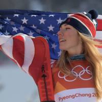 Mikaela Shiffrin raises the U.S. flag as she poses on the podium during the victory ceremony for the women's giant slalom at the Yongpyong Alpine Centre. | AFP-JIJI