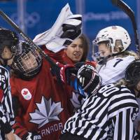 Canada forward Marie-Philip Poulin (29) battles with United States forward Monique Lamoureux-Morando (7) as Canada goaltender Genevieve Lacasse, center, had her helmet taken off during the third period of a preliminary round women's hockey game. | AP