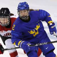 Aina Takeuchi of Japan  and Emmy Alasalmi of Sweden during a women's ice hockey classification match. | REUTERS