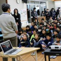 School's in: Children gather to watch a music video collaboration, some of who appeared in it with Ugandan elementary school students, after the presentation at Toyotama Minami Elementary School in Tokyo's Nerima Ward. Sixth graders from the school have been corresponding with Ugandan children since 2016. | KYODO