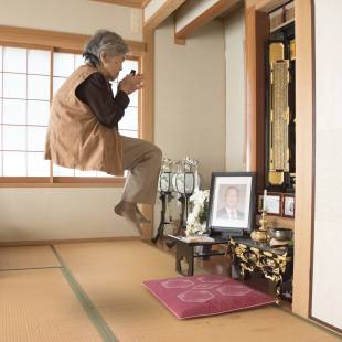 Photographer Kimiko Nishimoto poses for a self-portrait in front of a family altar at her home in Kumamoto.