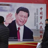 People walk past a poster of Chinese President Xi Jinping in Beijing on Monday. Xi's tightening grip on China had already earned the leader comparisons to Mao Zedong, but they came into even sharper focus after the party on Sunday paved the way for him to assume the presidency indefinitely. | AFP-JIJI