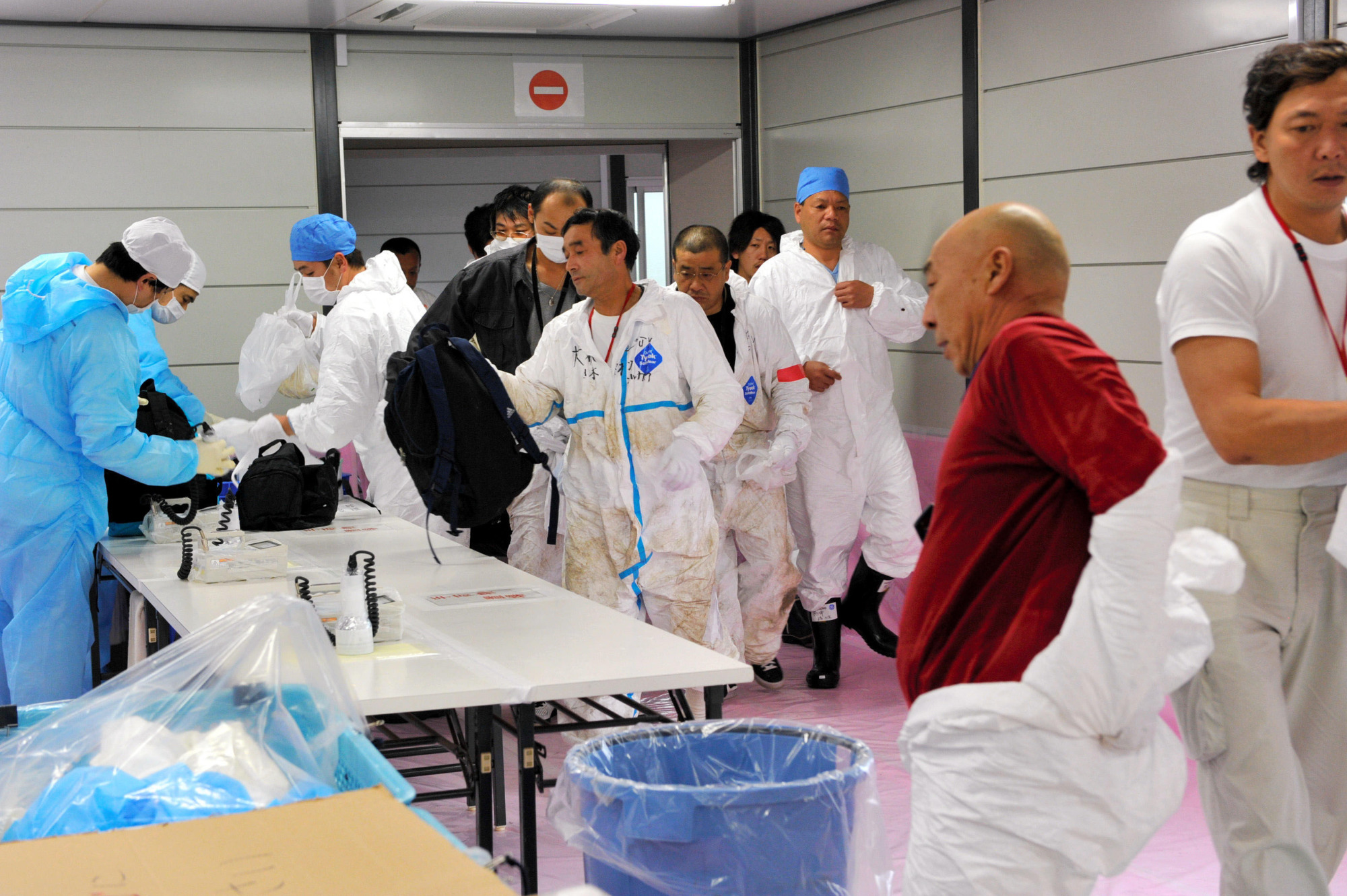 Front-line fight: Workers remove protective clothing after a shift at the Fukushima No. 1 nuclear plant in November 2011. | KYODO