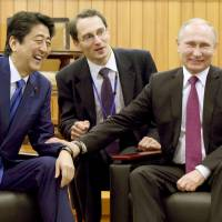 Prime Minister Shinzo Abe and Russian President Vladimir Putin share a light moment at the Kodokan Judo Institute in Tokyo on Dec. 16, 2016. It was during this visit to Japan by Putin that the two leaders first began discussing a special system for economic cooperation in the Northern Territories. | VIA BLOOMBERG
