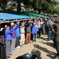People take part in a rally in front of Camp Schwab in Nago, Okinawa, on Dec. 26 as the sit-in protest against the relocation of U.S. Marine Corp's Futenma air station from Okinawa's Ginowan city to Nago reached 5,000 days. | AFP-JIJI