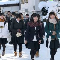 Students walk to a test site in Yonezawa, Yamagata Pref., to take the National Center Test for University Admissions on Jan. 13. Starting in the 2020 academic year, that test will be replaced with a new unified university entrance exam that aims to test students' ability to think, judge and express themselves. | KYODO
