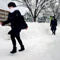 Hopefuls trudge through the snow on their way to take a national standardized university admissions test in the city of Niigata on Jan. 13. Young people in Japan would benefit greatly by developing a 'go for it' attitude toward life. | KYODO