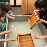 Ozu Washi instructor Nao Tanaka demonstrates how to pick up a film of pulp that will eventually dry into a sheet of paper. | DANIELLE DEMETRIOU