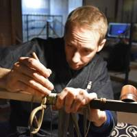 Sharp artisanship: Hans Koga works on a sword, carefully removing, cleaning and replacing parts and ensuring that the piece is retains its original style. | KYODO