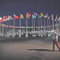 A volunteer walks past flags at the Medals Plaza in Pyeongchang, South Korea, on Feb. 16. | REUTERS