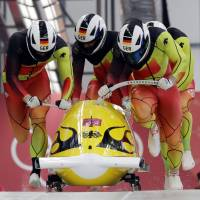 (From left) driver Francesco Friedrich, Candy Bauer, Martin Grothkopp and Thorsten Margis of Germany start their third heat in the four-man bobsled final on Sunday at the Pyeongchang Olympics. They won the gold medal. | AP