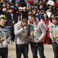 German driver Francesco Friedrich (left) and teammates Candy Bauer, Martin Grothkopp and Thorsten Margis celebrate their gold-medal victory in the four-man bobsled final during at medals ceremony on Sunday. AP