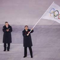 Beijing Mayor Chen Jining holds the Olympic flag during the Pyeongchang Games closing ceremony as IOC president Thomas Bach applauds on Sunday night at Pyeongchang Olympic Stadium.