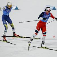 Norway's Marit Bjoergen (right) and Sweden's Stina Nilsson compete in the women's 4x5-km relay cross-country skiing race  in Pyeongchang, South Korea on Saturday. | AP