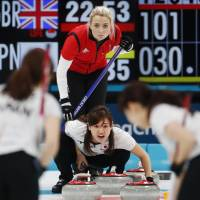 Japan's Chinami Yoshida of Japan and Britain's Anna Sloan compete in a women's round-robin match at Gangneung Curling Centre on Tuesday. | REUTERS