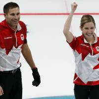 Canada's Kaitlyn Lawes and John Morris celebrate their gold medal in the mixed doubles curling final against Switzerland on Tuesday at Gangneung Curling Center. | REUTERS