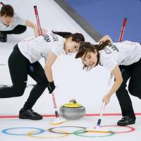 Yurika Yoshida (left), Chinami Yoshida (right) and Yumi Suzuki (rear) compete for Japan during the women's curling competition at the Pyeongchang Olympics. Japan defeated Denmark 8-5 on Thursday in Gangneung, South Korea. | KYODO