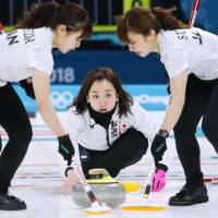Japan skip Satsuki Fujisawa (center) watches the shot as Yurika Yoshida (left) and Yumi Suzuki sweep during their match against the Olympic Athletes from Russia on Saturday night in Gangneung, South Korea. | KYODO