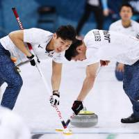 Japan's Kosuke Morozumi (left) and Tetsuro Shimizu sweep the ice during a preliminary round match against South Korea on Wednesday. | KYODO