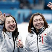 Skip Satsuki Fujisawa (left) and teammate Mari Motohashi react after Japan's 5-3 triumph over Great Britain in the women's bronze-medal match at Gangneung Curling Center on Saturday night. | REUTERS