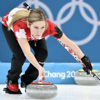 Canada's Kaitlyn Lawes delivers the stone in the mixed doubles final on Tuesday against Switzerland. | REUTERS