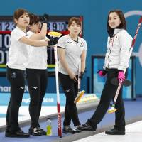 The Japan women's curling squad strategizes in the fifth end of the bronze-medal match on Saturday night. | KYODO