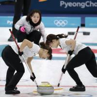 Japan's Chinami Yoshida (left) and Yurika Yoshida sweep the ice in the match against Great Britain. | AP