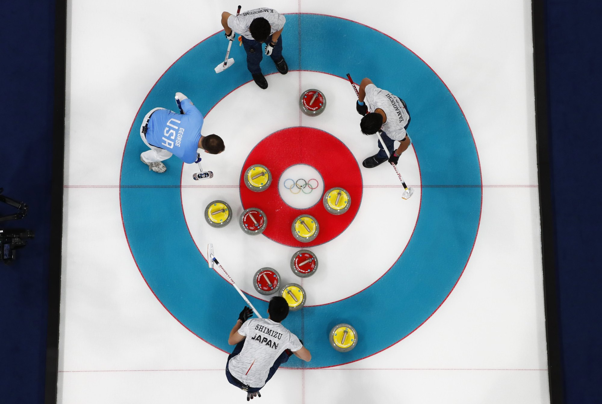 Yusuke Morozumi (top) Tsuyoshi Yamaguchi (right) Tetsuro Shimizu (bottom) and American Tyler George compete in the men's Olympic curling competition on Sunday. | REUTERS