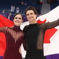 Tessa Virtue and Scott Moir celebrate after winning the ice dance title at the Pyeongchang Olympics on Tuesday in Gangneung, South Korea. | REUTERS