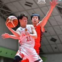 Diamond Dolphins guard Takaya Sasayama passes the ball as NeoPhoenix big man Atsuya Ota defends in the third quarter on Sunday in Toyohashi, Aichi Prefecture. Nagoya rallied to beat San-en 77-74. | B. LEAGUE