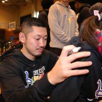 Kumamoto Volters guard Shintaro Kobayashi, an active figure in the B. League's outreach to Kumamoto youth in the aftermath of the April 2016 earthquakes, signs an autograph during All-Star weekend last month. | B. LEAGUE
