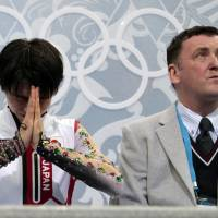 Yuzuru Hanyu (left) waits for his scores with coach Brian Orser during the men's free skate at the 2014 Sochi Olympics on Feb. 14, 2014. | AP