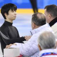 Yuzuru Hanyu speaks to coach Brian Orser during Monday's practice. | KYODO